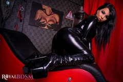 Mistress-Elenia-in-latex-on-couch-looking-over-shoulder