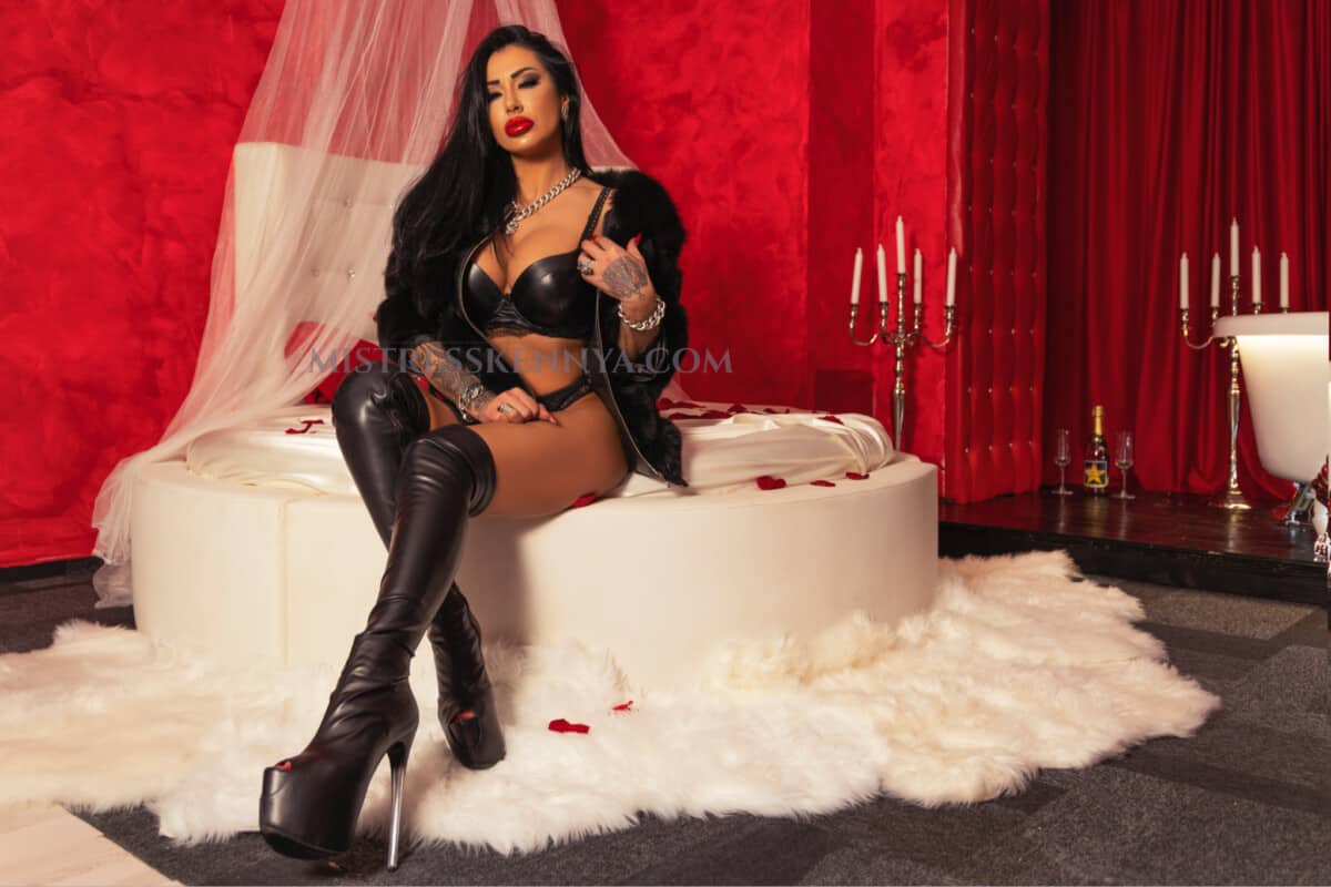 Mistress Kennya in leather lingerie and boots  on the bed
