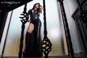 Looking up to Mistress Kennya lying with leather dress and leather boots